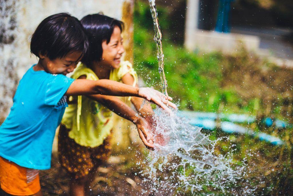Niños jugando felices con agua